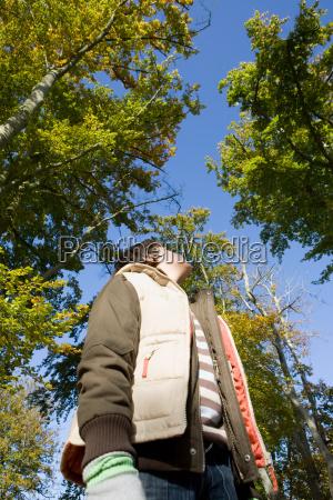 boy looking up at tree