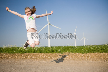 girl jumping near wind farm