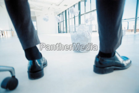businessman throwing paper into bin