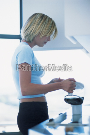 office worker pouring coffee into cup