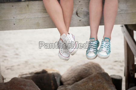 young women sitting on pier on
