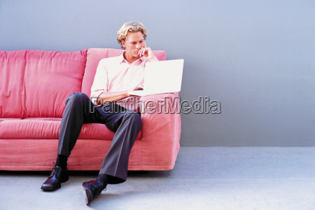 man on sofa using laptop computer