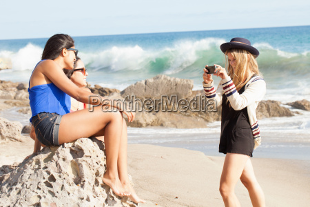three young women taking photographs on
