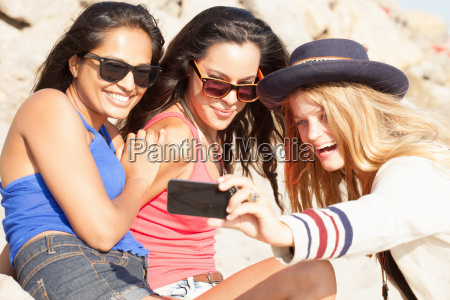 three young women taking smartphone selfie