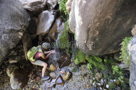 female hiker drinking from waterfall mount
