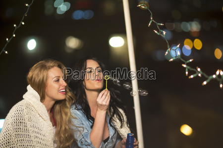 two female friends blowing bubbles at
