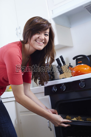 young woman in kitchen preparing food