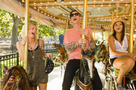 three young adult friends riding horse