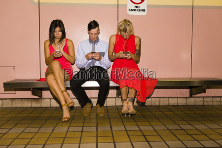 three young adult friends texting on