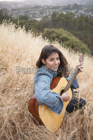 portrait of young woman playing acoustic