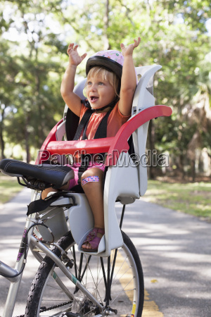 young girl sitting in childs bicycle