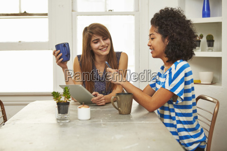young female friends with smartphone and