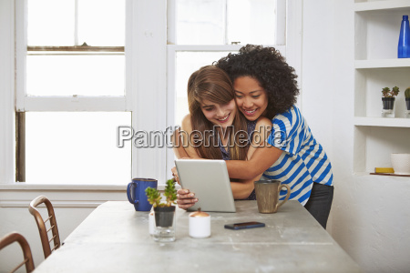 young female couple looking at digital