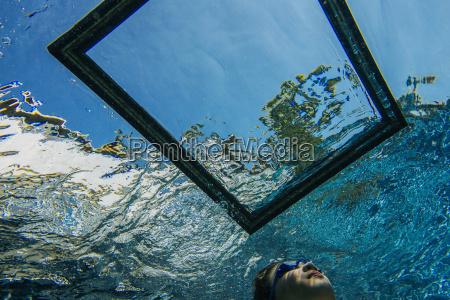 teenage girl underwater looking through frame