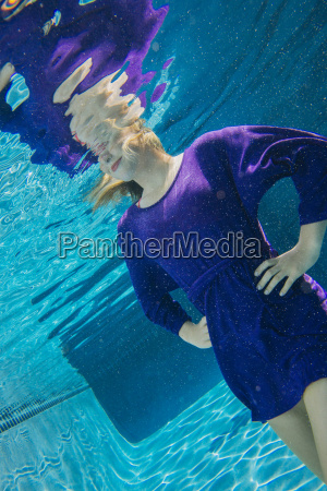young woman underwater hands on hips