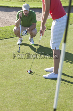 young female lining up golf ball