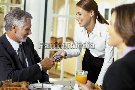 waitress handing cellphone to businessman