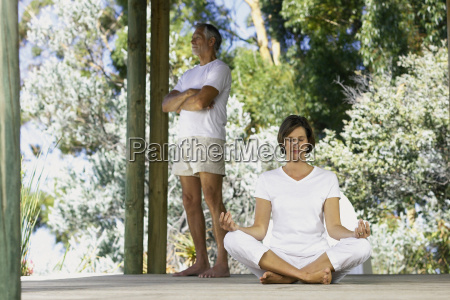 woman doing yoga outside with man