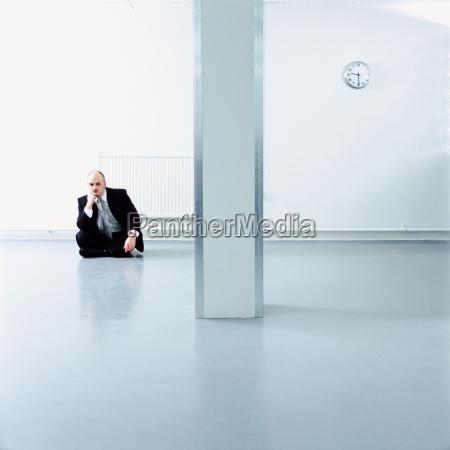 a businessman sat on a floor