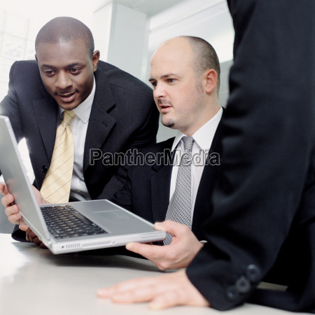 businessmen looking at a laptop