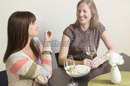 mid adult female friends drinking white
