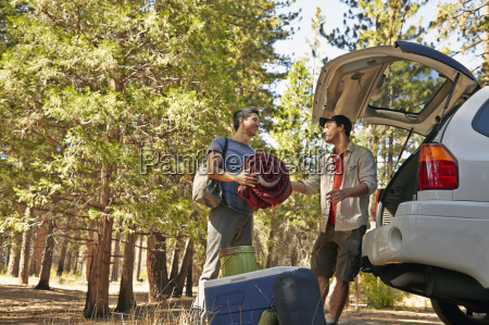 two young male campers unpacking car