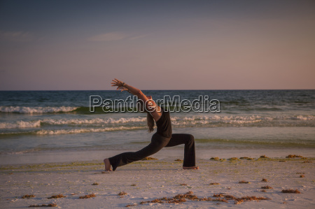 mature woman practicing yoga on beach