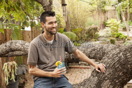man sitting on branch in garden