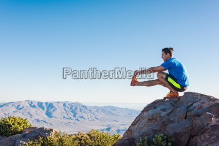 male trail runner stretching legs on