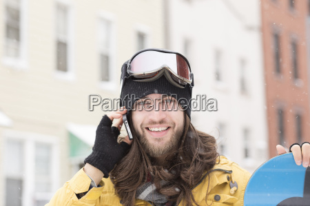 portrait of young man holding snowboard