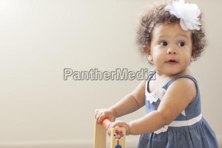 portrait of baby girl pushing baby