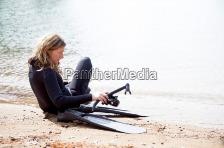 mid adult female scuba diver preparing