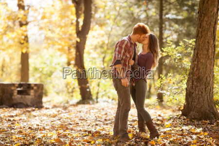 young couple kissing in autumn forest