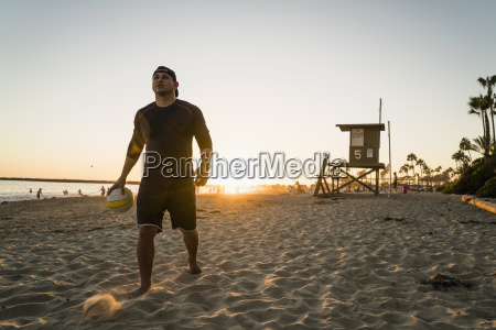 young man playing beach volleyball at