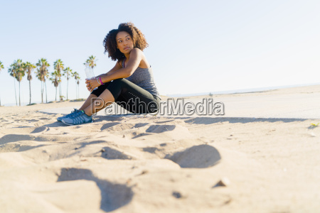 mid adult woman sitting on beach