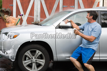 couple having fun washing car
