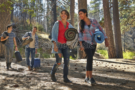 four young adult friends walking in