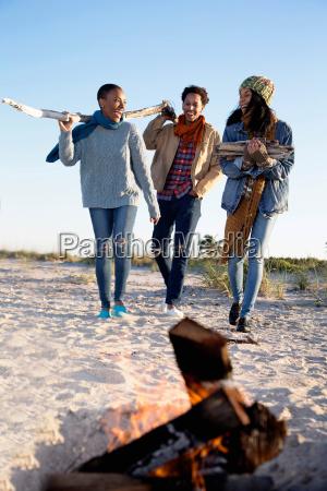 three friends on beach gathering drift