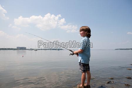 young boy fishing on beach
