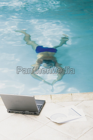 man in swimming pool with computer