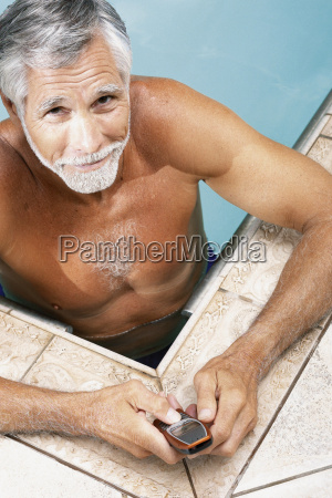 man in swimming pool with cellphone