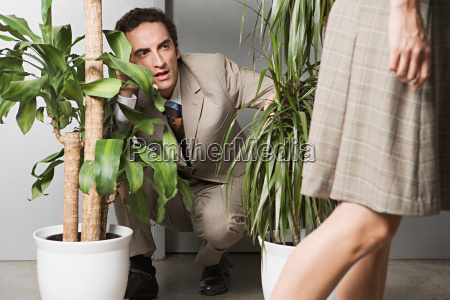 man hiding in plants and watching