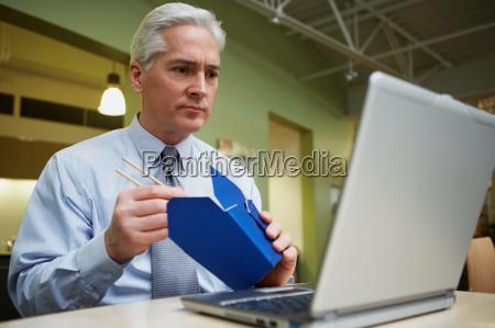 man eating chinese food at desk