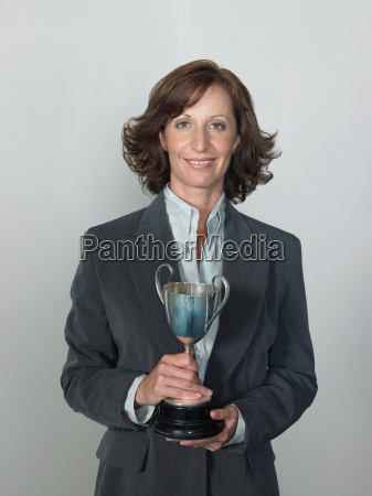 businesswoman holding a trophy