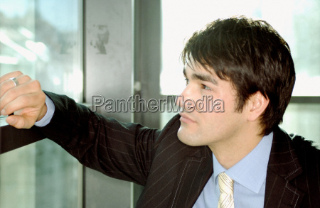 businessman leaning against window