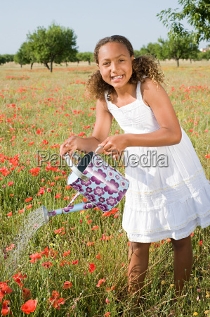 young girl watering poppy field with