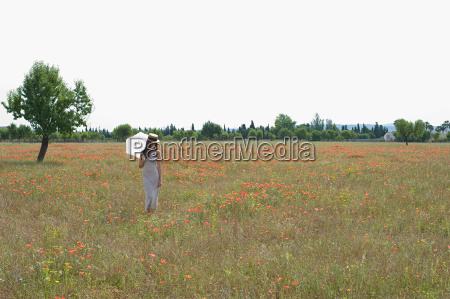 young woman standing in poppy field
