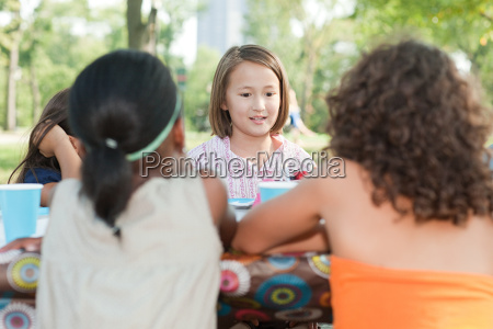children sitting at picnic table at