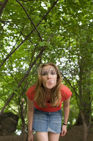 teenage girl blowing a bubble gum