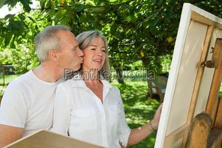 mature couple woman painting at easel